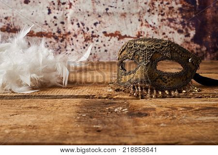 venetian carnival mask with a white feathers on wooden table