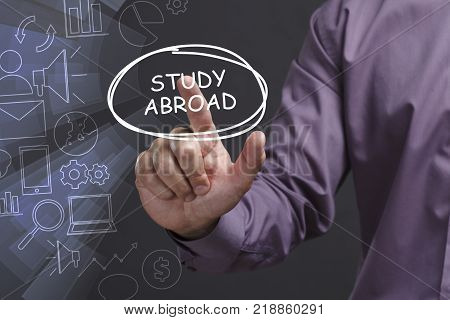 Business, Technology, Internet And Network Concept. Young Businessman Shows The Word: Study Abroad