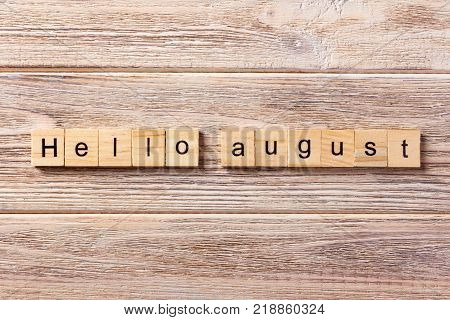 hello august word written on wood block. hello august text on table concept.