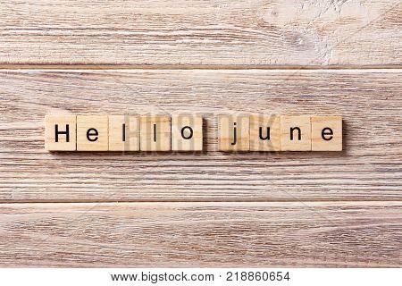 Hello June word written on wood block. Hello June text on table concept.