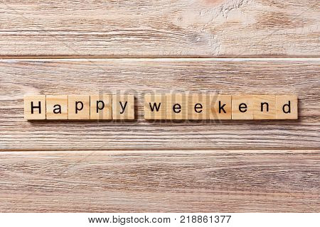 happy weekend word written on wood block. happy weekend text on table concept.