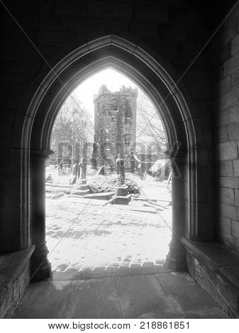 the ruined church of heptonstall through an archway in falling snow