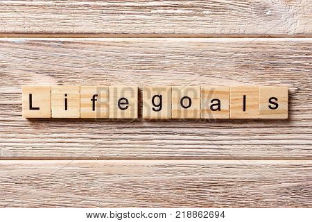 LIFE GOALS word written on wood block. LIFE GOALS text on table concept.