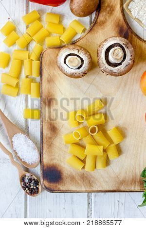 Vegetables and rigatoni pasta on wooden board. Top view