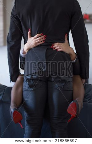 Couple have sex on sofa closeup woman with red nails embracing man