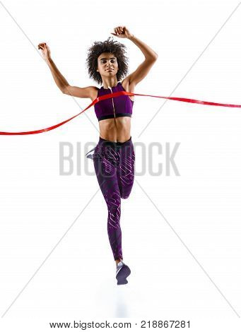 Woman running crossing finish line. Photo of young african woman isolated on white background. Sport and healthy lifestyle. Dynamic movement. Competition event