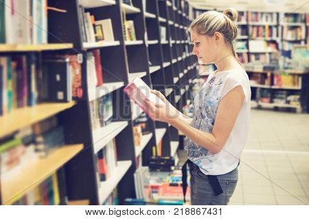 young woman choosing a book to buy in bookstore