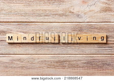 mindful living word written on wood block. mindful living text on table concept.