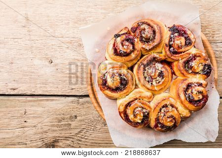 Homemade delicious cinnamon rolls with lemon and berries over wooden background, top view