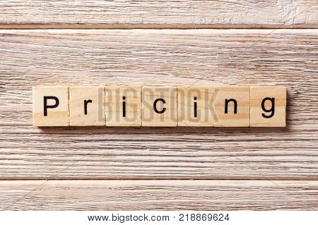 Pricing word written on wood block. Pricing text on table concept.