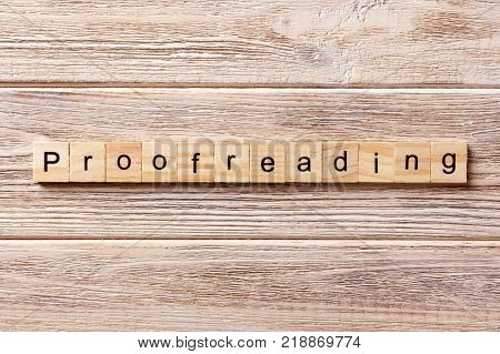 proofreading word written on wood block. proofreading text on table concept.