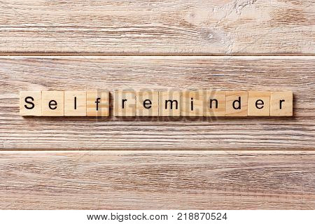 self reminder word written on wood block. self reminder text on table concept.