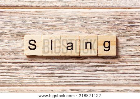 slang word written on wood block. slang text on table concept.