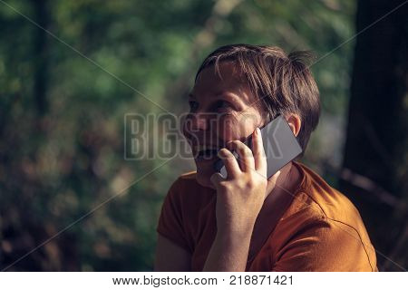 Happy smiling woman talking on mobile phone outdoors in park on sunny summer afternoon