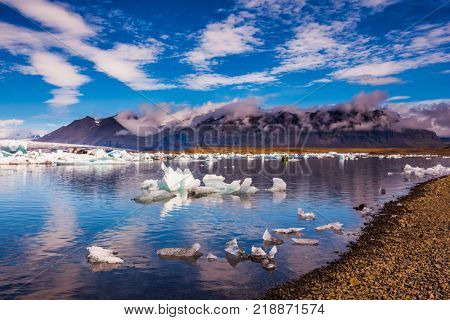 The ice floes and cirrocumulus clouds of lagoon Jokulsarlon, Iceland.  Cirrocumulus magically reflected in the smooth water of the lagoon. The concept of northern extreme tourism