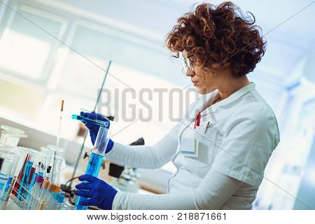 Female scientist using test tube with blue liquid sample substance probe in the scientific chemical research laboratory