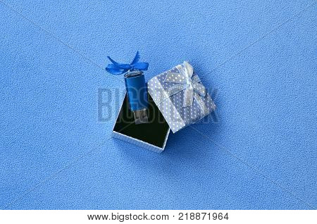 Brilliant blue usb flash memory card with a blue bow lies in a small gift box in blue with a small bow on a blanket of soft and furry light blue fleece fabric. Classic female gift memory card design
