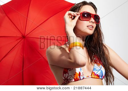 A young girl in sunglasses with a parasol behind