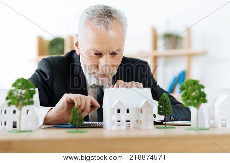 Very attentive. Clever experienced reliable real estate agent sitting in his office and looking attentively at the model of a wonderful house in the countryside while planning how to sell it