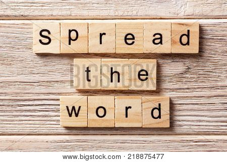 Spread the word word written on wood block. Spread the word text on table concept.