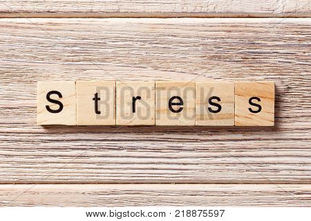 Stress word written on wood block. Stress text on table concept.