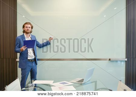 Western Businessman Presenting A Project On Blank Glass Board In Meeting Room