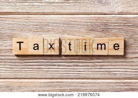 tax time word written on wood block. tax time text on table concept.