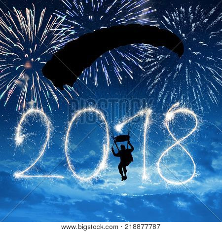 Silhouette skydiver parachutist landing in to the New Year 2018