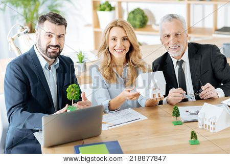 Productive morning. Emotional enthusiastic real estate agents sitting at the table in their office and looking happy while showing pretty realistic miniature houses and trees