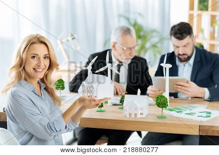 Cheerful woman. Cute emotional friendly woman looking glad and showing a nice model of a house while her enthusiastic colleagues sitting by her side and working at the progressive windmill turbines