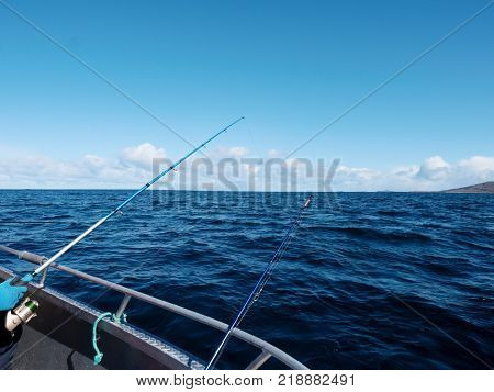 Fishing boat with fishing rods floating in open sea. Background beautiful sky. Sport sea fishing