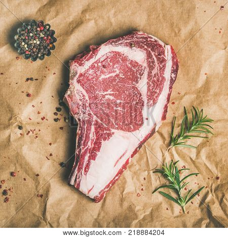 Flat-lay of raw uncooked prime beef meat dry-aged steak rib-eye on bone with seasoning on craft paper over grey concrete countertop background, top view, square crop. Meat high-protein dinner concept