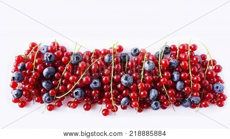 Ripe blueberries and red currants mint isolated on a white. Berries at border of image with copy space for text. Red and blue berries. Various fresh summer berries on white background. Top view.