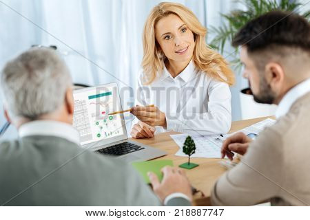 Clear examples. Smart pretty skilled woman feeling confident while pointing to the screen of her convenient modern laptop and showing the advantages of her project
