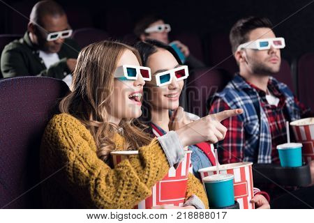 young smiling friends in 3d glasses with popcorn watching film in movie theater