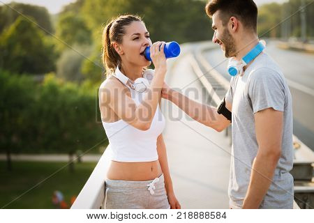 Cute and young couple staying hydrated after workout