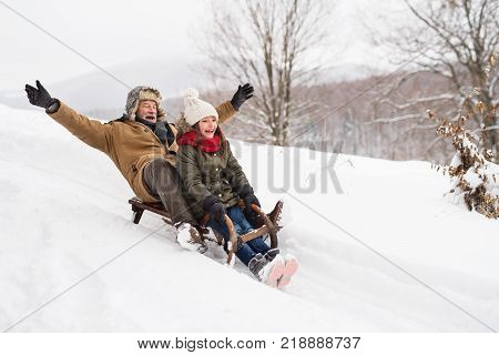 Senior grandfather and a small girl sledging, having fun. Winter day.