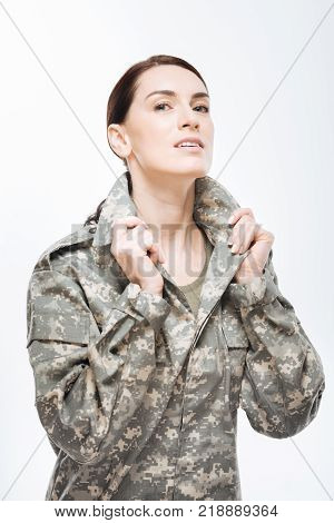 Combat uniform. Pleasant appealing brunette woman placing  collar of combat jacket while gazing  at the camera and  standing  on the  isolated  background