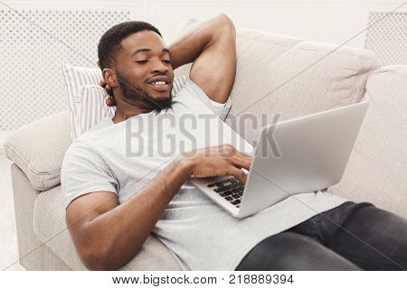 Young african-american man surfing the web on laptop. Smiling boy in casual lying on couch in light appartment, copy space