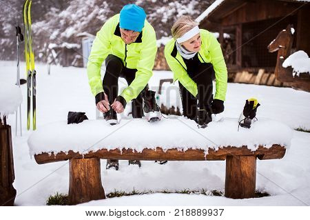 Active senior couple getting ready for cross-country skiing. A man and woman putting on ski boots. Winter time.