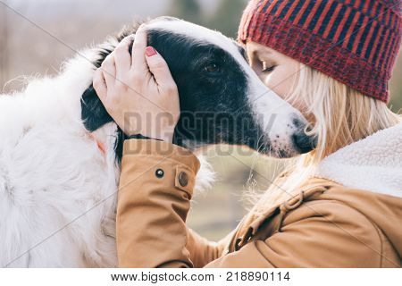 Girl embracing her dog. Young woman and her dog having fun together.