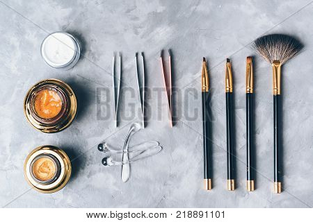 A set of tools accessories and cosmetic for the care of the eyebrows on grey background. Brushes combs brow gel brow scrub tweezers.