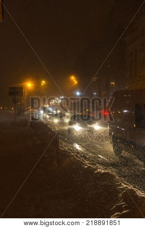 A car driving on the road in the aggravated traffic due to strong snowfall. City blizzard. City light, night.