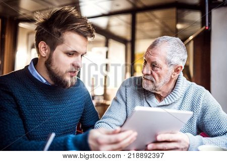 Senior father and his young son with tablet in a cafe.