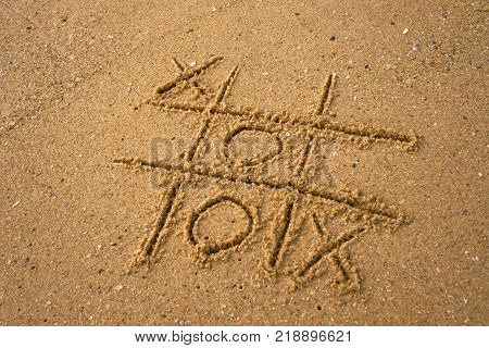 tic-tac-toe drawing in sand background. Concept of winning and success
