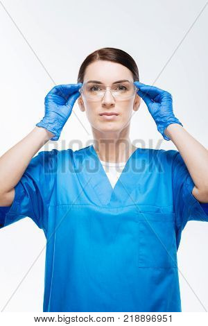 Difficult surgery. Earnest focused female doctor gazing at the camera  while putting on glasses and dressing in gloves