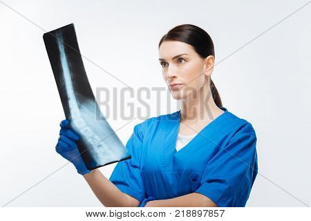 Spine problem. Earnest nice female doctor  worrying about scan and  gazing at it while standing  on the isolated background