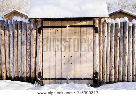 Old House In The Siberian Forest Fenced With Palisade Snow