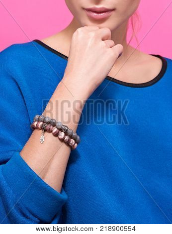 Handmade bracelet on the arm of a young woman. Blue sweater and neutral pink background
