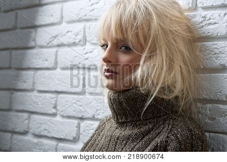 Blonde haired beautiful young woman posing seductively near the wall looking playfully to the camera copyspace devilish flirting erotic look feminine confident attraction.